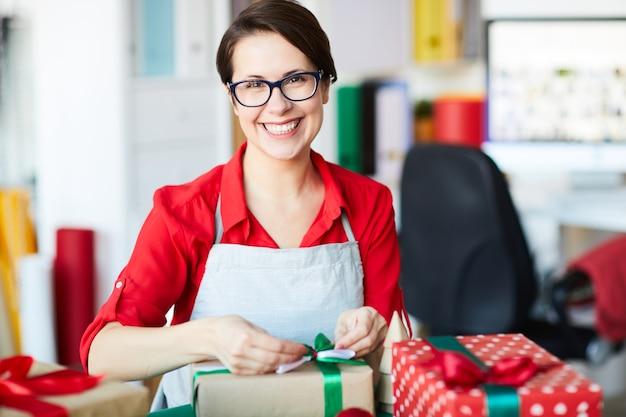 Счастливая женщина, упаковка рождественских подарков или подарков