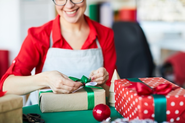 Happy woman wrapping christmas gifts or presents