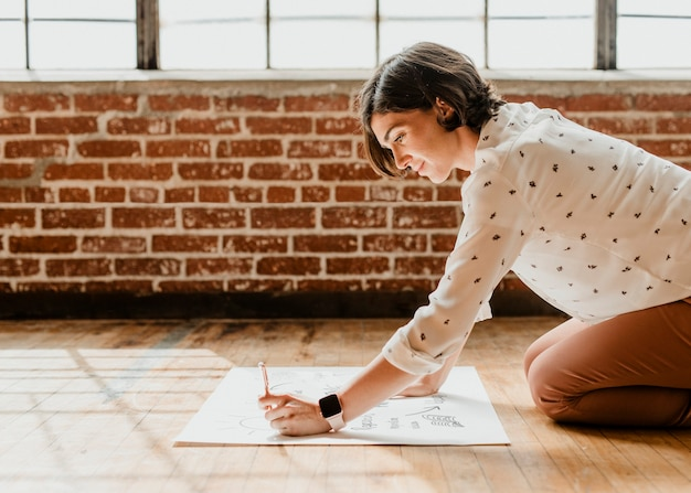 Happy woman writing on a white chart paper on the floor