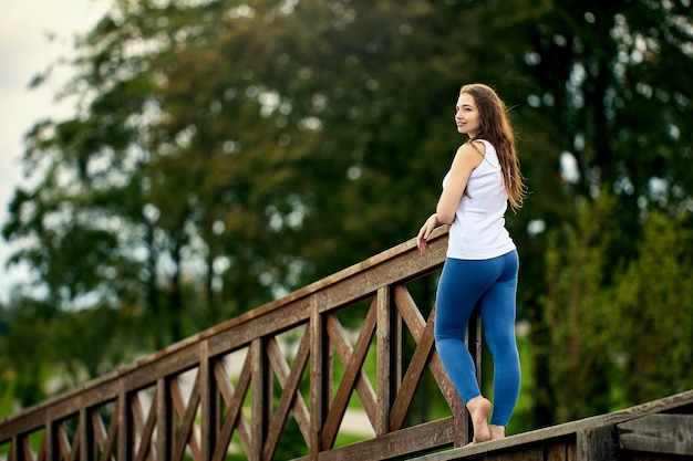 Счастливая женщина лет стоит в парке в летний день