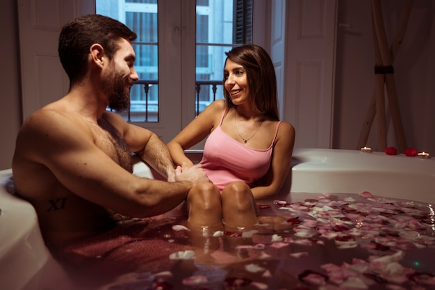 Happy woman and young man in spa tub with water