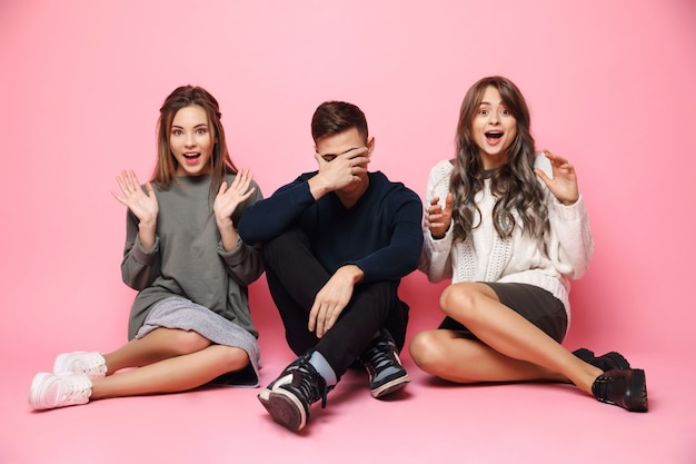 Happy womans and sad guy sitting on pink floor