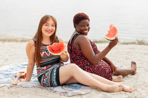Happy women at the beach enjoying watermelon