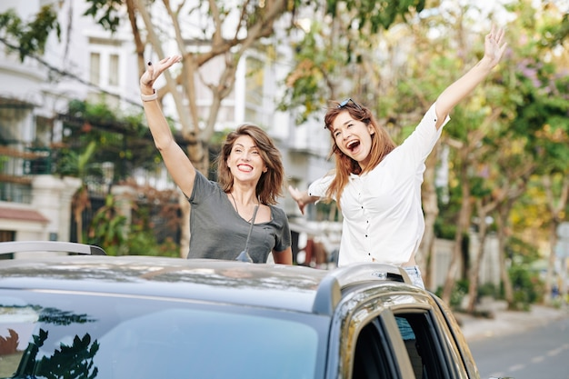 Happy women catching taxi