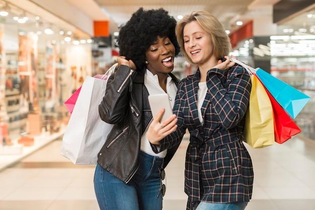 幸せな女性が買い物の後、電話をチェック