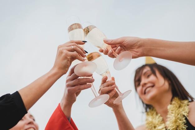 Счастливые женщины поднимают бокалы с шампанским на вечеринке на крыше