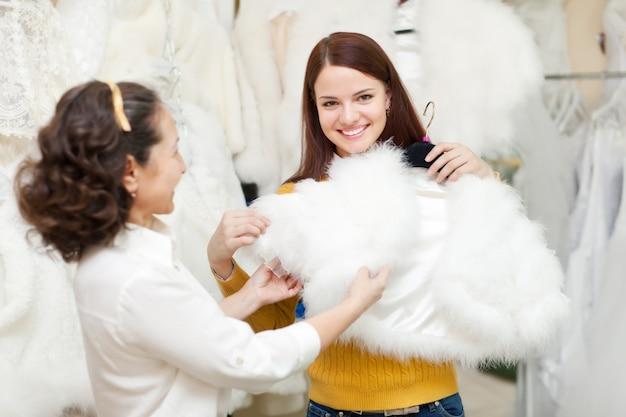 幸せな女性は結婚式の店で毛皮の岬を選ぶ