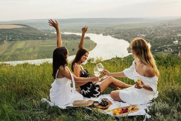幸せな女性は、水面に川がある山で白ワインとグラスをチリンと鳴らします。
