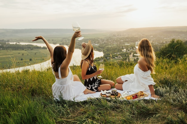 幸せな女性は川のある山で白ワインとグラスをチリンと鳴らします