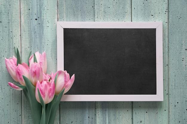 Меловая доска с надписью «happy women day» и розовыми тюльпанами, плоско лежала на светло-зеленых досках.