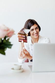 ノートパソコンでアイシャドウパレットを表示する幸せな女性