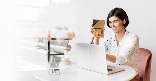 Happy women displaying an eye shadow palette with a laptop