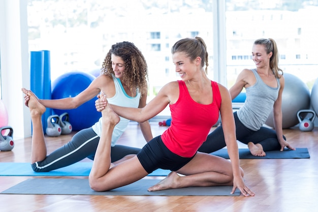 Happy women doing pigeon pose with one hand right leg grab