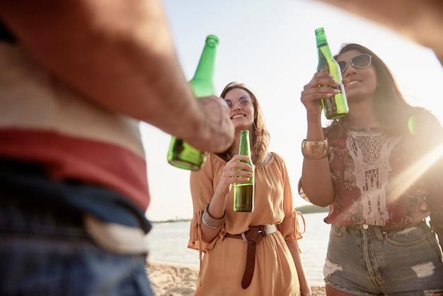해변 파티에서 맥주를 마시는 행복한 여성