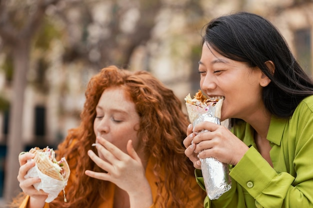 Happy women eating together street food