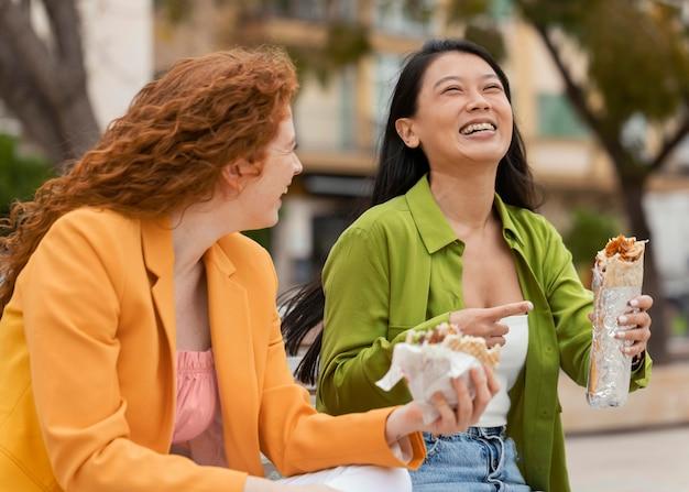 一緒に屋台の食べ物を食べる幸せな女性
