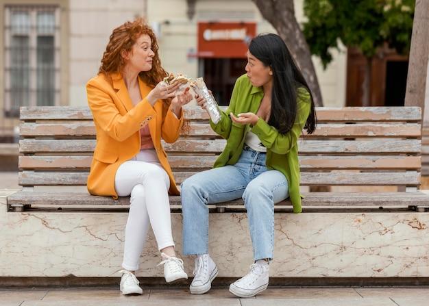 Счастливые женщины вместе едят уличную еду