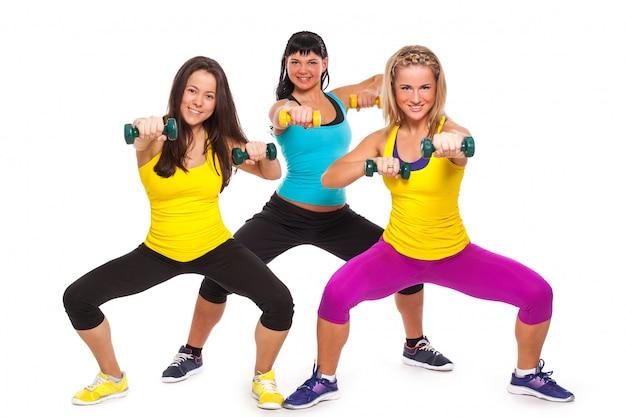 Happy women in fitness wear with dumbbells