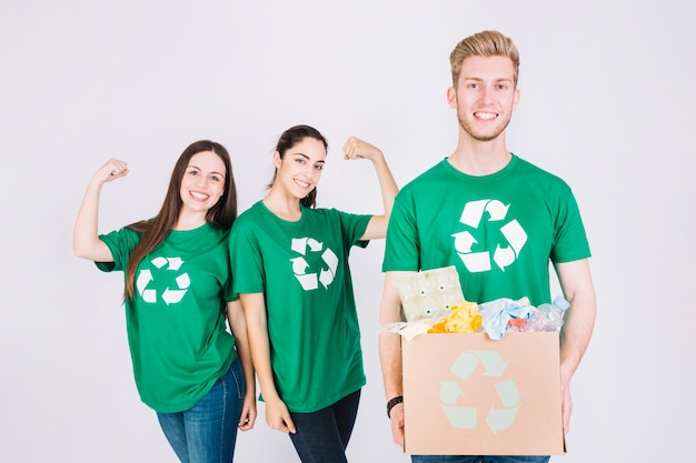 Happy women flexing their muscles behind man holding recycle items cardboard box