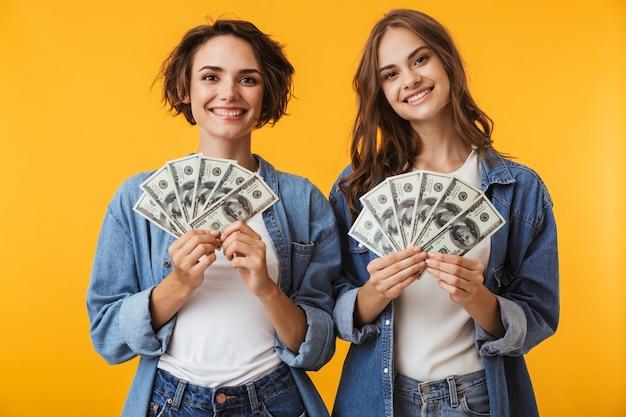돈을 들고 노란색 벽 위에 절연 행복 한 여자 친구.