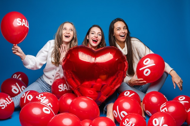 Happy women friends posing with red heart shaped balloon and air balls with percent and sale lettering on blue backdrop