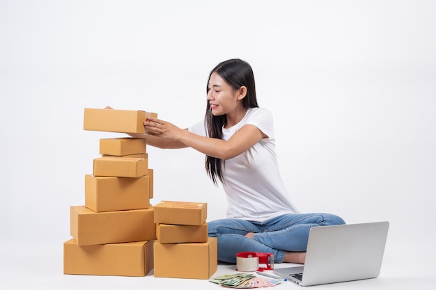 고객으로부터 제품을 주문하여 행복한 여성, 집에서 흰색 찾기로 일하는 사업자