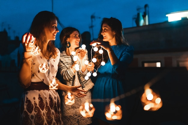 Happy women having fun at rooftop party with lights at night