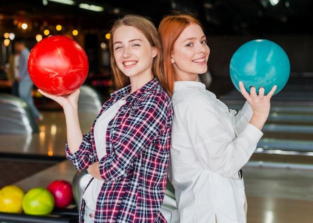 ボウリングのボールを保持している幸せな女性