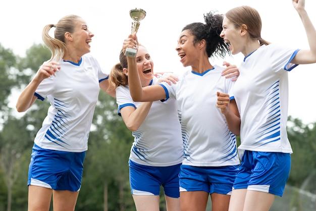 ゴールデンカップを保持している幸せな女性