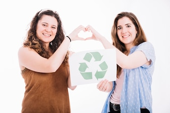 Happy women holding recycle placard making heart sign with hands