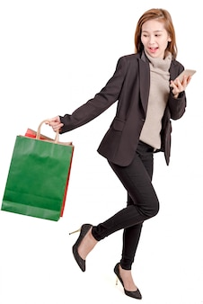 Happy women hole bag and smartphone for shopping