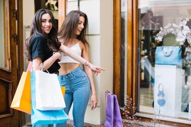 Happy women lookin at bag behind shop-window