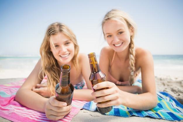 Счастливые женщины, лежащие на пляже с пивной бутылкой