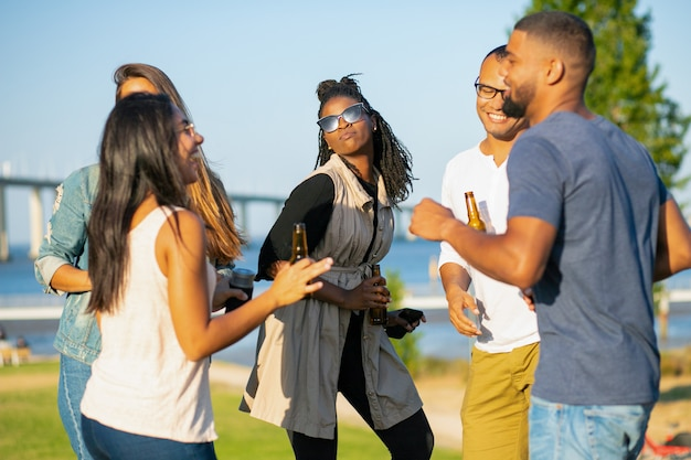 Happy women and men dancing in park in evening. cheerful friends relaxing with beer during sunset. leisure concept