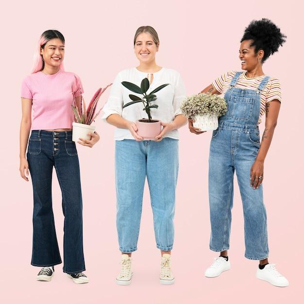 幸せな女性は鉢植えの観葉植物を保持している愛好家を植えます