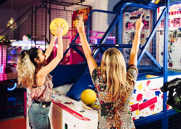 Happy women playing basketball arcade game