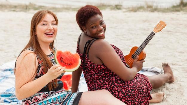 Счастливые женщины позируют на пляже с арбузом и гитарой