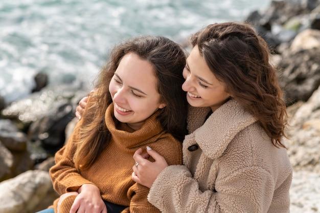 Счастливые женщины вместе позируют на скале Premium Фотографии