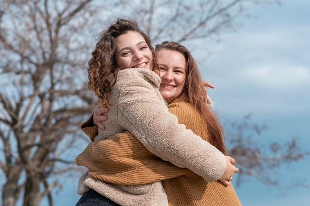 屋外で一緒にポーズをとって幸せな女性 Premium写真