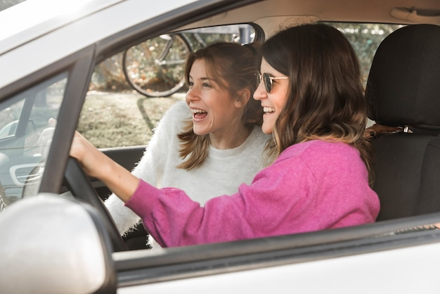 Happy women riding car