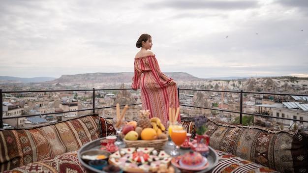 Happy women on rooftop of cave house enjoying of goreme city panorama, cappadocia turkey.