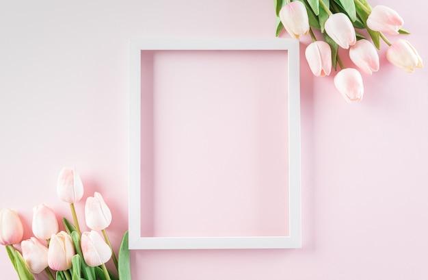 행복 한 여성의 날 개념, 파스텔 배경에 흰색 액자와 핑크 튤립.