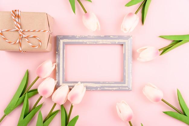 幸せな女性の日、母の日のコンセプト。トップビューフラットレイアウトフォトフレーム、ギフトボックス、チューリップの花