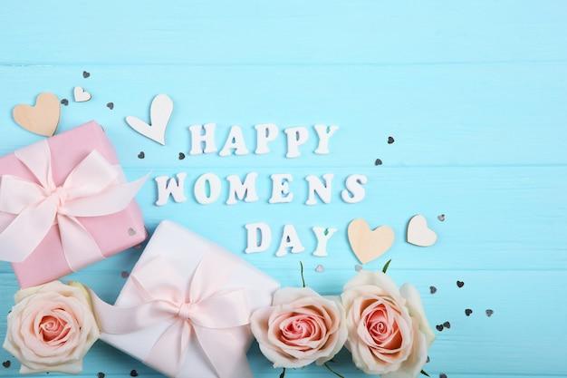 Счастливый женский день текст с розами, сердцами и подарками на синем фоне