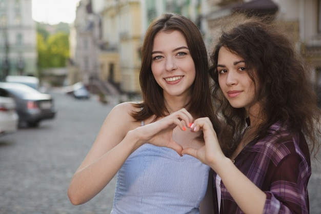 Happy women smiling to the camera, showing a heart with their hands, copy space