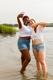 Happy women taking selfie at the beach