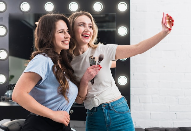 Happy women taking selfie in makeup mirror