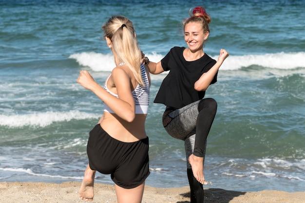 幸せな女性がビーチで一緒にトレーニング