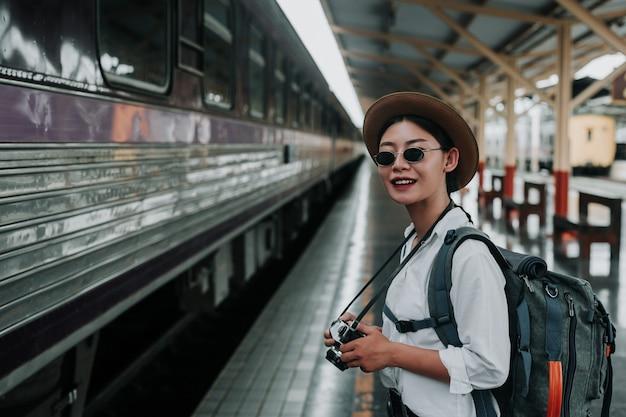 電車、休暇、旅行のアイデアで旅行する幸せな女性。