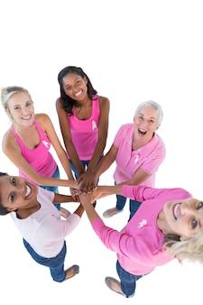 乳がんのためにピンクとリボンを着けている幸せな女性たちは、一緒に手をカメラで見上げている